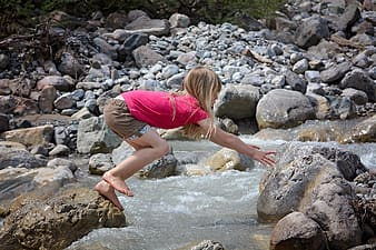 Girl at rock jumping and reaching another stone