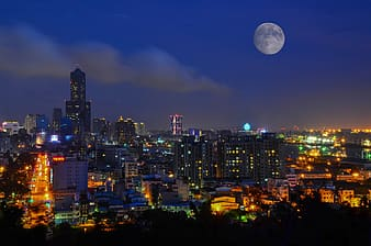 City buildings under full moon during