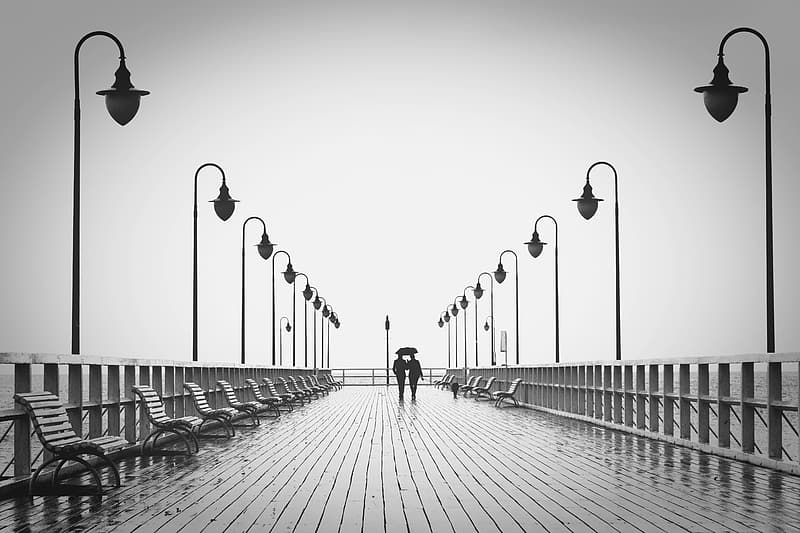 Man and woman standing surrounded by light posts grayscale photograph