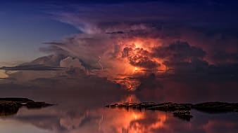 Reflection of lightning on body of water during golden hour