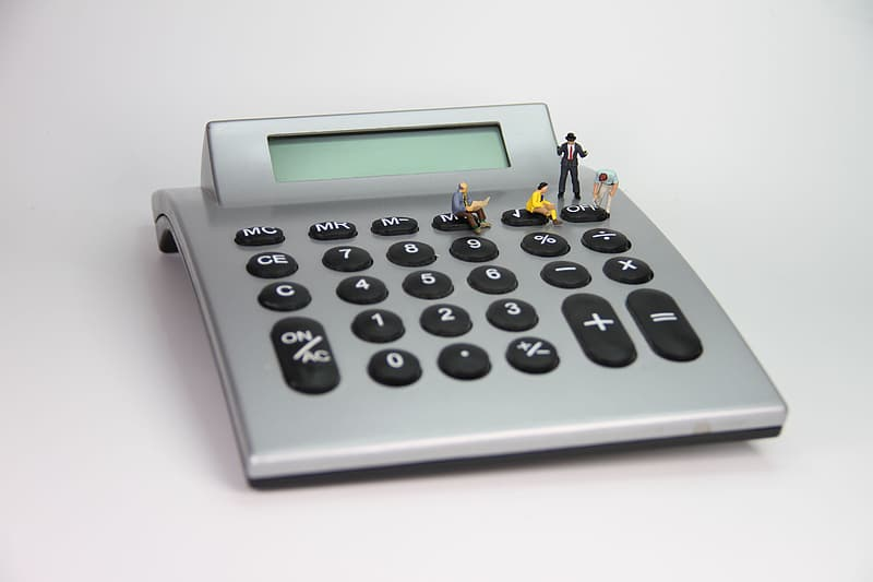 Four figurines on turned off calculator