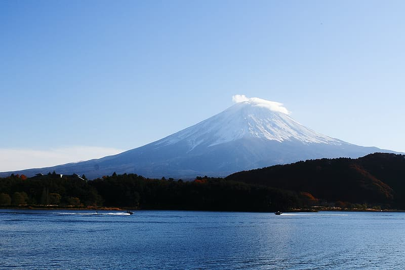 Calm body of water near mountain and volcano under blue sky at daytime