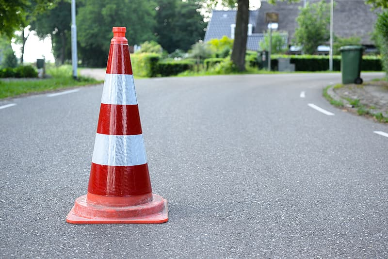 Red and white traffic cone on gray asphalt road during daytime