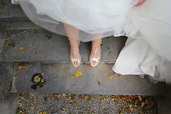 Woman in white dress and white leather peep toe sandals