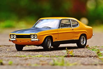 Selective focus photo of classic yellow coupe scale model