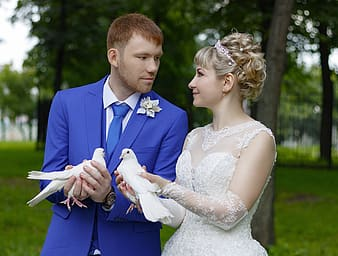 Woman and woman facing each other while holding white doves