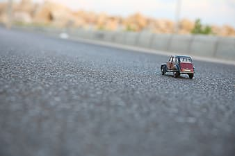 Macro shot of red and black car toy on ground