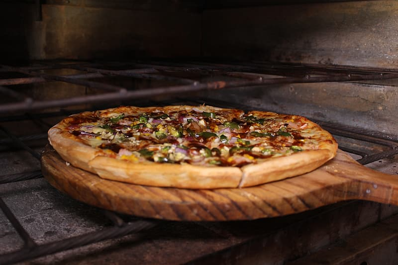 Baked pizza on brown wooden pizza pan putting on oven