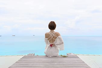 Woman in white dress sitting on wooden dock during daytime