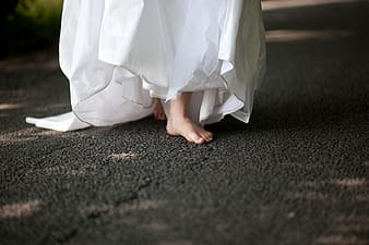Woman wearing white dress walking on black area rug