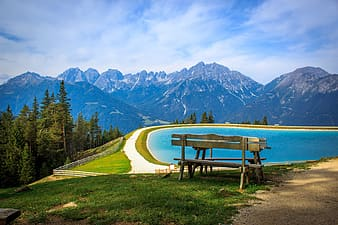 Brown wooden bench near body of water painting