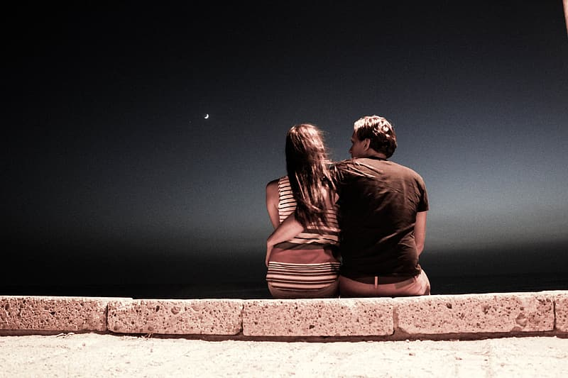 Man and woman sitting on gray concrete pavement during night