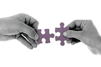 Two person holding purple puzzles