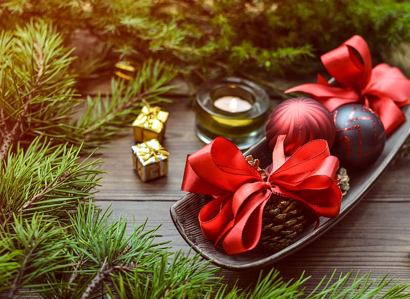 Red and black baubles beside conifercone