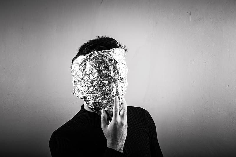 Grayscale photo of man with foil wrap on his face