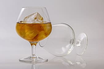 Clear wine glass with half-filled with liquor and ice