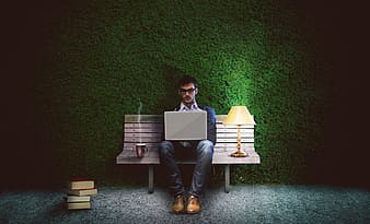 Man in black shirt and pants sitting on brown wooden bench using macbook