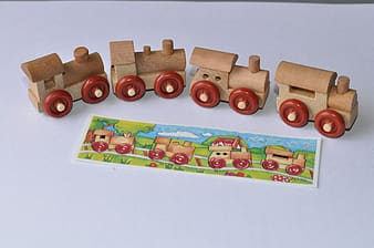 Brown-and-red wooden toy train on white surface