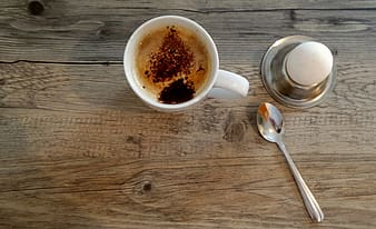White ceramic mug beside silver spoon on brown wooden table