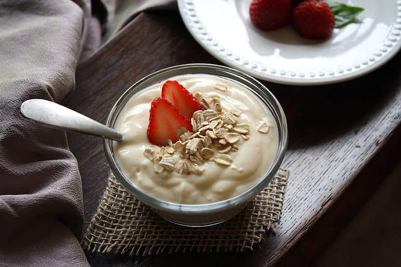 Clear glass cup filled with white desert and sliced strawberry