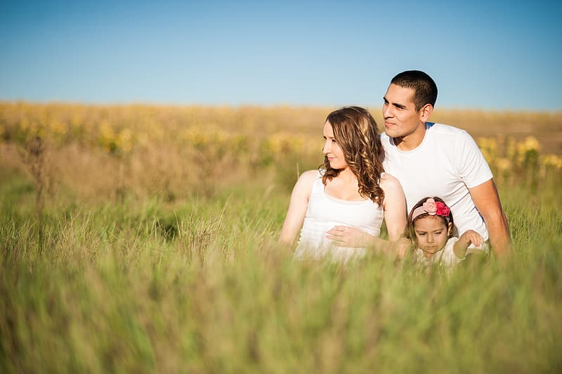 Man, woman and child sitting on grass field during daytime