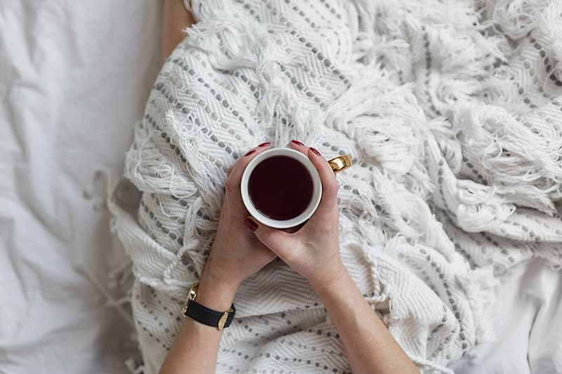 Soft photo of woman on the bed with the book and cup of coffee in hands