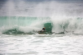 Man on body of water with wave