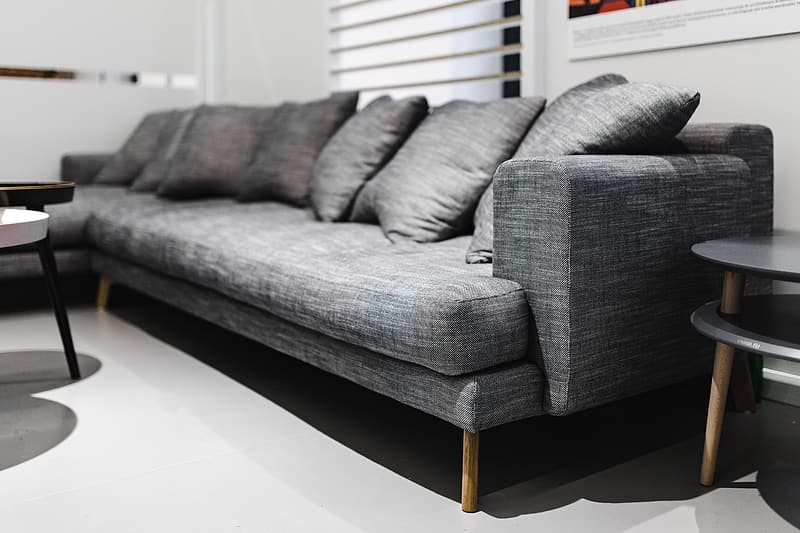 Gray and black couch on white ceramic floor tiles