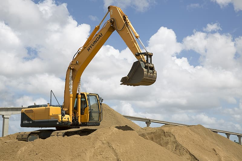 Yellow and black excavator on brown hill under white clouds and blue sky during daytime