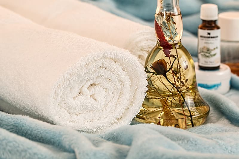 Rolled bath towel beside brown liquid filled bottle