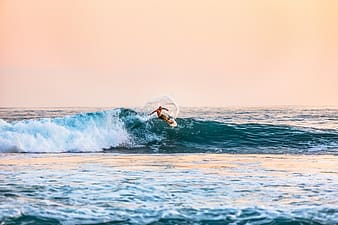Person surfing on ocean waves during daytime
