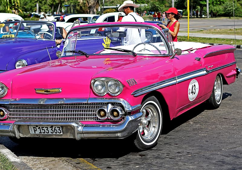 Classic pink convertible car parked on parking space