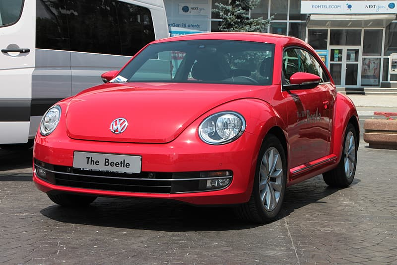 Red Volkswagen New Beetle coupe parked next to white vehicle at daytime