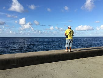 Man carrying sling bag standing near body of water