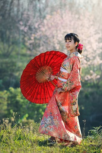 Woman wears pink and multicolored floral dress holds red folding umbrella