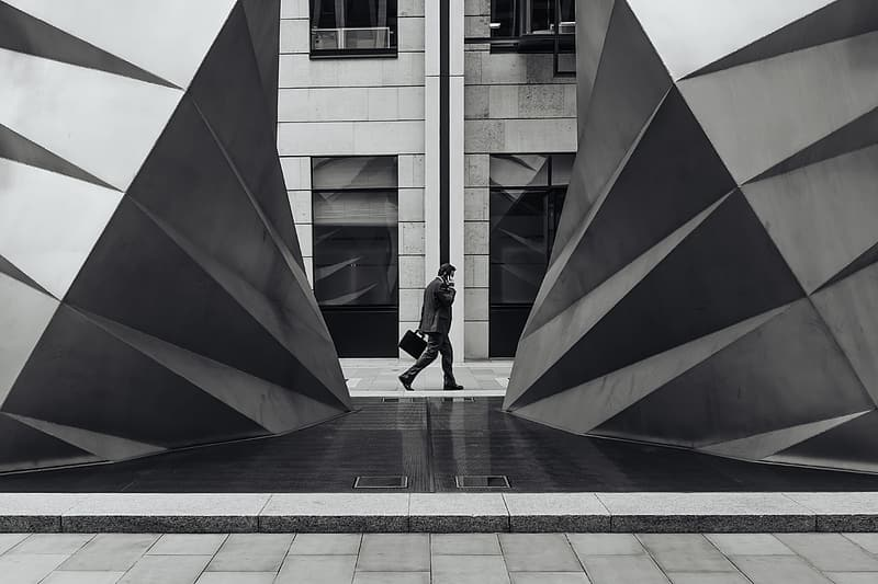 Grayscale photo of man walking beside building