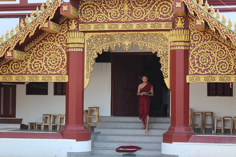 Man wearing red traditional dress standing on stair