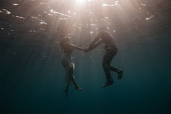 Man and woman holding hand while floating on water