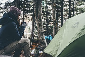 Woman in blue jacket holding blue cup while sitting near green tent in forest