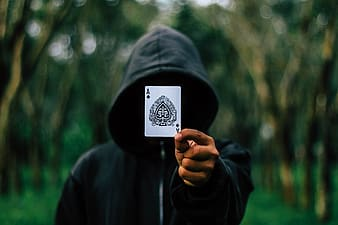 Person holding ace of spade card