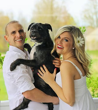 Man and woman carrying dog looking on camera