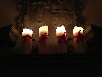 Four lighted white pillar candles