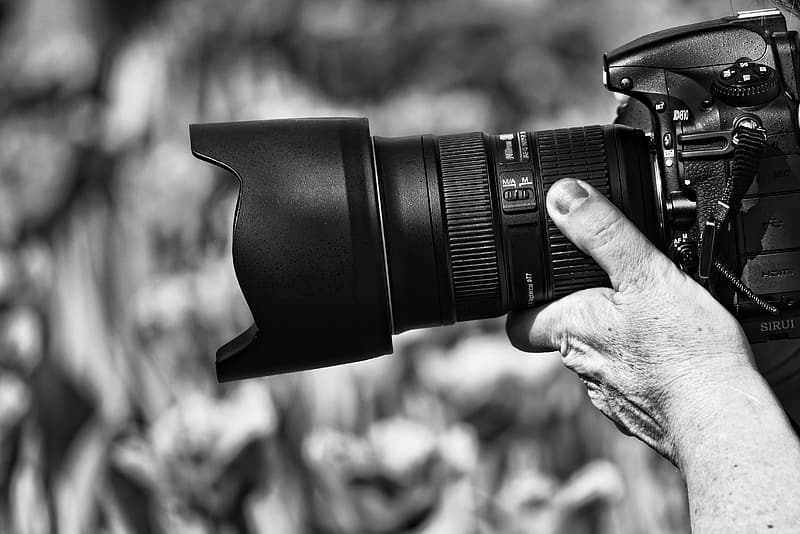Grayscale photograhy of person taking photo using DSLR camera