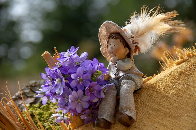 Photo of purple flowers beside gray doll during daytime