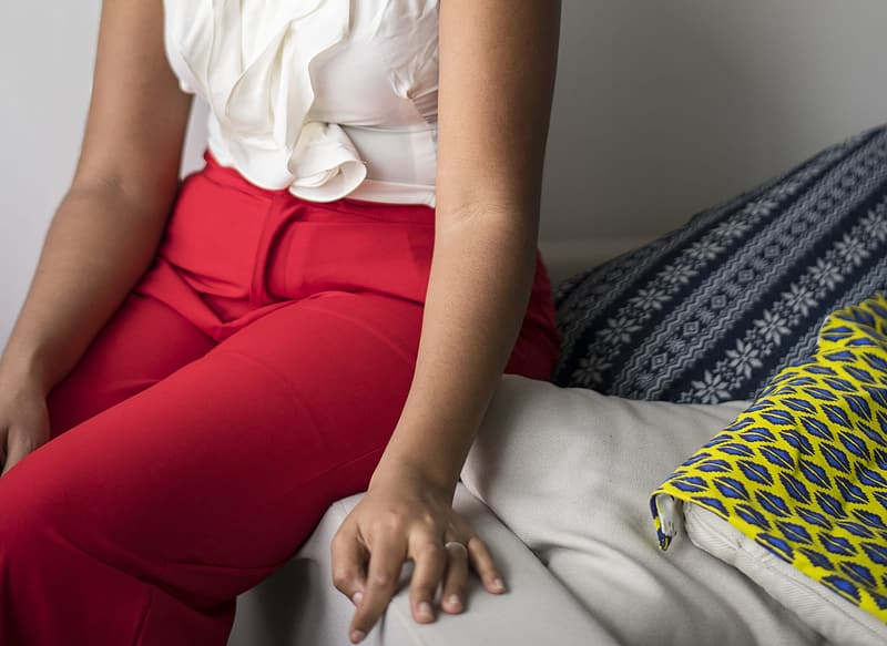 Woman in white shirt and red pants sitting on bed