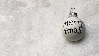Merry Xmas printed bauble on silver surface