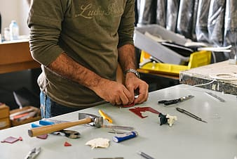 Man in brown crew neck t-shirt holding yellow and black hand tool