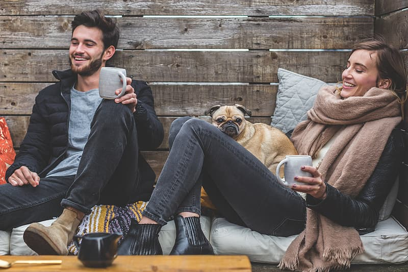 Man wearing black zip jacket sitting beside woman with brown scarf and fawn pug on woman's lap