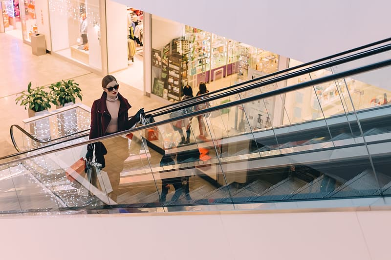 Woman carrying bags while standing on escalator