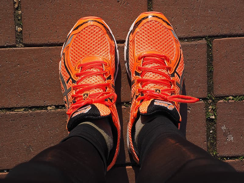 Closeup photo of person wearing orange-and-black running shoes